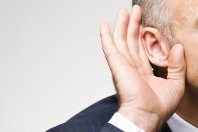 Man in suit cupping his ear with his hand